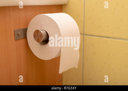 Toilet paper rolled up on a roll in the toilet. Personal hygiene products. Light background. - Stock Photo