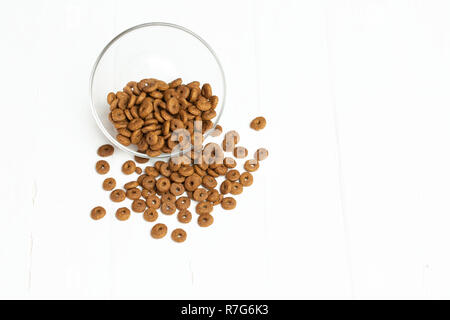 Dry cat food poured out of a transparent bowl on a white background - Stock Photo