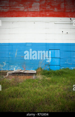 Red white & blue painted stripes on exterior warehouse wall. - Stock Photo