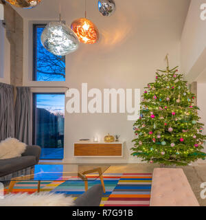 Contemporary open plan living space in home with double height windoes, Tom Dixon lights and Christmas tree. - Stock Photo