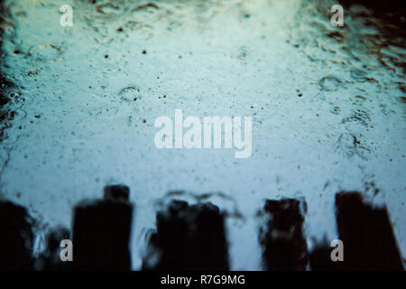 Water droplets on car windshield in car wash. - Stock Photo