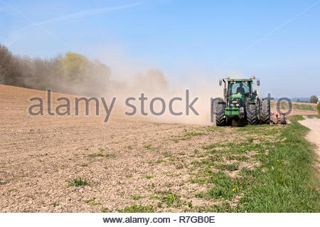 Tractor with cultivator prepares field for seeding. - Stock Photo