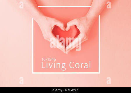 Female hands in shape of heart toned in Living Coral color. Color of the year 2019. - Stock Photo