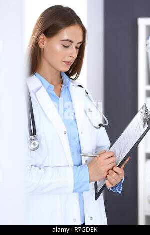 Doctor woman filling up medical form while standing near window in hospital office. Happy physician at work. Medicine and health care concept - Stock Photo