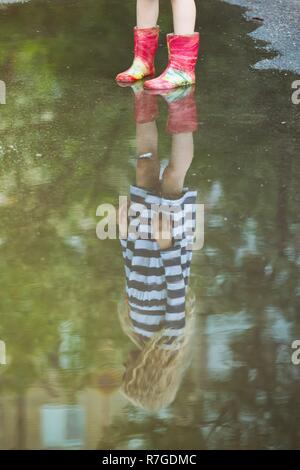girl in gumboots is reflected in a puddlel, summer - Stock Photo