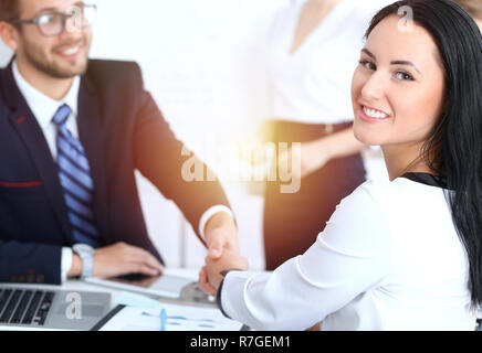 Business handshake at meeting or negotiation in the office. Two businesspeople partners are satisfied because signing contract or financial papers - Stock Photo