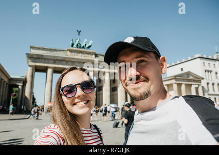 Young beautiful couple making selfie against the background of the Brandenburg Gate in Berlin in Germany. - Stock Photo
