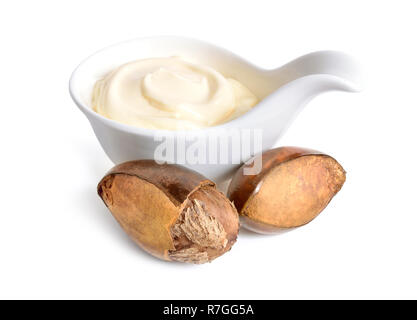 Shea nuts with butter or cream in the bowl. Isolated on white background. - Stock Photo