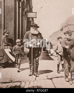 Life for working folk in Victorian days... A blind man with his white stick and an entourage of kids in Great Homer Street, Liverpool, Merseyside, England - Stock Photo