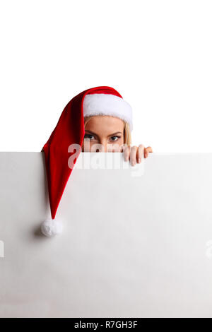Christmas woman peeking over edge of white billboard with copy space for text - Stock Photo
