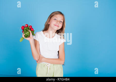 beautiful little girl radishes holds food vegetables - Stock Photo