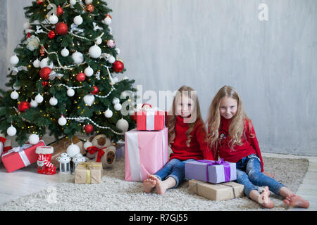 two small girls blonde in red dress at Christmas gifts new year holiday - Stock Photo