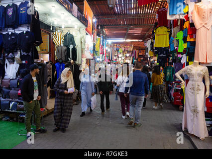 Marrakech souk - local people and tourists shopping in the souks; the Marrakesh Medina, Marrakech, Morocco, North Africa - Stock Photo