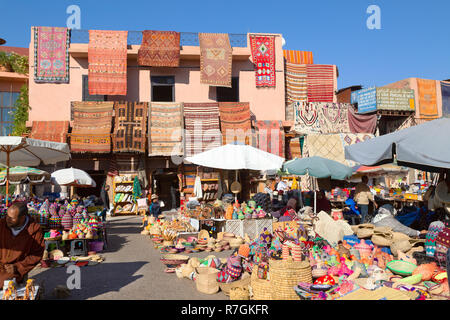 Marrakech souk - colourful goods and carpets for sale in the souks, Marrakech medina, Marrakesh Morocco Africa