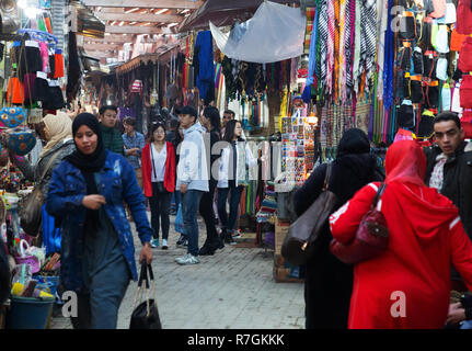 Tourists and local people shopping and buying goods in the souk, Marrakech Medina, Marrakesh, Morocco Africa - Stock Photo