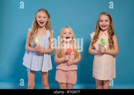 three beautiful young girls and sweet candy lollipops - Stock Photo