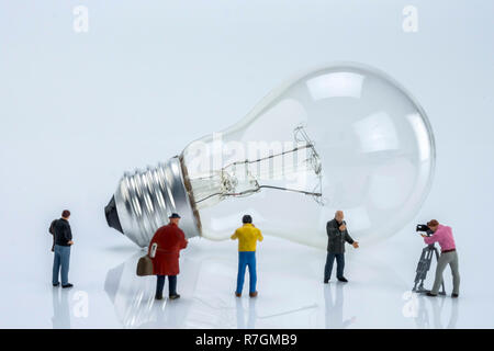 Miniature figures near a light bulb, conceptual image - Stock Photo