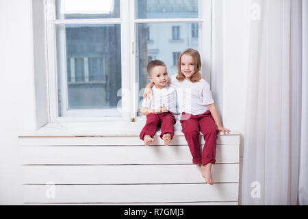 little boy and girl sit on the windowsill looking out the window - Stock Photo