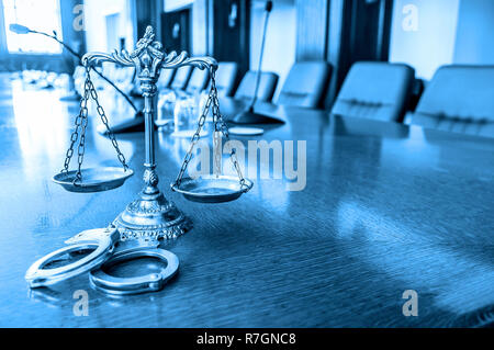 Scales of Justice and  handcuffs on the desk blue tone - Stock Photo