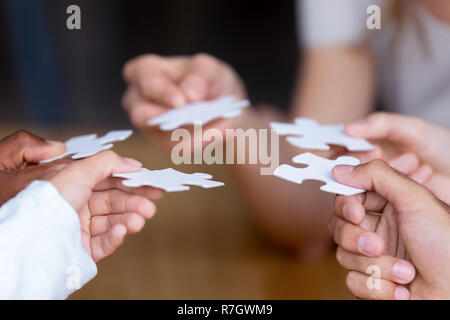 Hands of multinational people holding puzzle pieces - Stock Photo