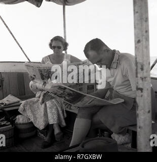 1950s, a man and wpman sitting on a boat on Lake Victoria, Uganda, reading a newspaper, The Daily Mail. The British daily newspaper in this era was a broadsheet and would be sent to British colonies and protectorates overseas, such as Uganda was, before the country became independent in 1962. - Stock Photo