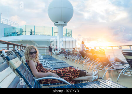 At Philipsburg, St Martin - December 1, 2016 : Blonde woman lying on sunbed in cruise ship during sunset. Stock Photo