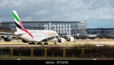 GATWICK AIRPORT, UK – DECEMBER 09 2018: An Emirates Airline A380 Airbus in front of the new commercial aviation hangar currently under construction. - Stock Photo