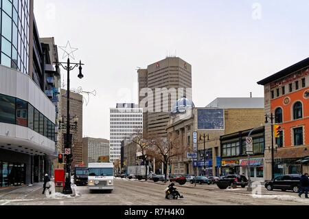Winnipeg, Manitoba, Canada - 2014 11 17: A person in a wheelchair crossing the intersection of Portage ave and Smith st in winter. - Stock Photo