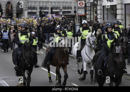 London, Greater London, UK. 9th Dec, 2018. Mounted police officers stand in front of the march against Tommy Robinson.Thousands of people took to the streets in central London to march against the 'Brexit Betrayal March' organised by Tommy Robinson and UKIP. Counter Protesters made their way from Portland Place to Whitehall, where speakers addressed the crowd. During the counter demonstration, there was a strong police presence. A group of counter protesters, who became separated from the main protest, were corralled by police to avoid an encounter with a group of Tommy Robi - Stock Photo