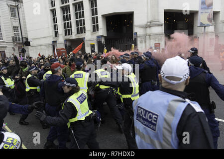 London, Greater London, UK. 9th Dec, 2018. Police officers contain protesters marching to Whitehall during the demonstration against the 'Brexit Betrayal March'.Thousands of people took to the streets in central London to march against the 'Brexit Betrayal March' organised by Tommy Robinson and UKIP. Counter Protesters made their way from Portland Place to Whitehall, where speakers addressed the crowd. During the counter demonstration, there was a strong police presence. A group of counter protesters, who became separated from the main protest, were corralled by police to av - Stock Photo