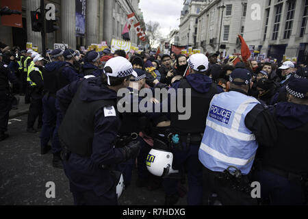 London, Greater London, UK. 9th Dec, 2018. Police officers contain a group of protesters marching to Whitehall during the demonstration against the 'Brexit Betrayal March'.Thousands of people took to the streets in central London to march against the 'Brexit Betrayal March' organised by Tommy Robinson and UKIP. Counter Protesters made their way from Portland Place to Whitehall, where speakers addressed the crowd. During the counter demonstration, there was a strong police presence. A group of counter protesters, who became separated from the main protest, were corralled by p - Stock Photo