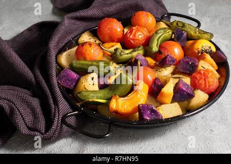 Rustic oven baked vegetables in black baking dish cooling on on dark towel on light gray concrete background. Seasonal vegetarian vegan meal. Ingredie - Stock Photo
