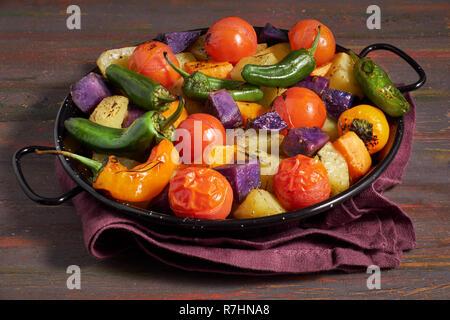 Rustic, oven baked vegetables in baking dish. Seasonal vegetarian vegan meal on dark wooden background with linen towel. Ingredients: potatoes, purple - Stock Photo