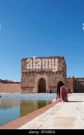 A long haired lady in pink sits by a calm pond in Morocco - Stock Photo