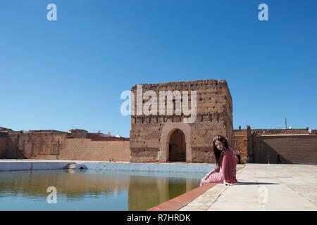 A brunette lady sits by a still pond in an ancient palace in Marrakech, Morocco - Stock Photo