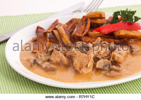 Turkey meat steamed with mushrooms and french fries on a plate and a light green cloth placemats. Decorated with red pepper and parsley. - Stock Photo