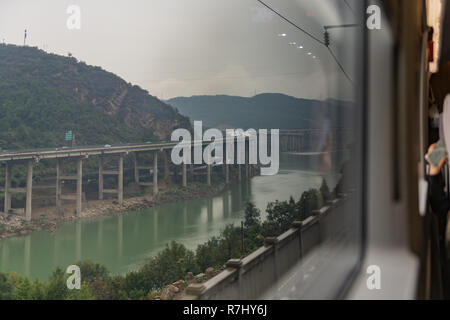 View from train window approaching small town  between Xian and Chengdu - Stock Photo