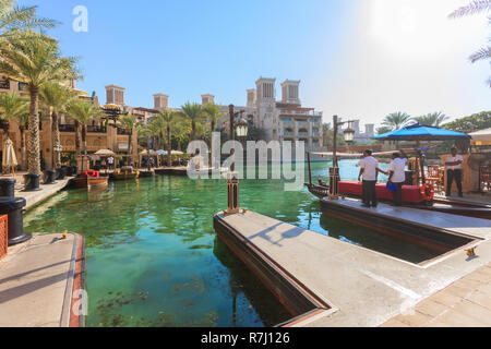 DUBAI, UAE - NOV 12, 2018: arabic architecture in Dubai souk Madinat Jumeirah with locals waiting for tourists to take by boat to visit Burj al Arab