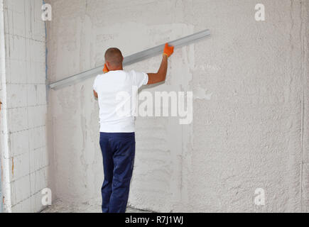 Worker plastering house walls,  finishing walls.  Wall screeding. Plastering walls techniques. - Stock Photo