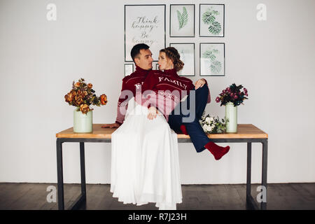 Romantic couple in red sweater with family word on table with flowers in vases. - Stock Photo
