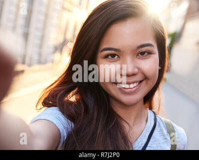 Content young Asian woman walking in the city taking selfies - Stock Photo