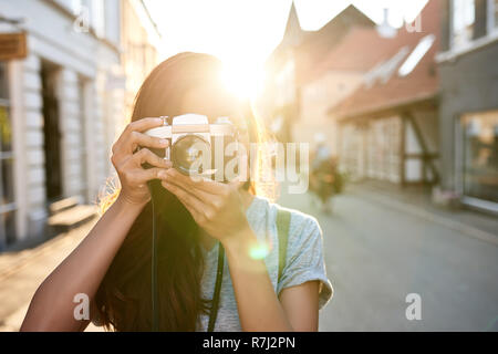 Young Asian woman taking photos in the city - Stock Photo