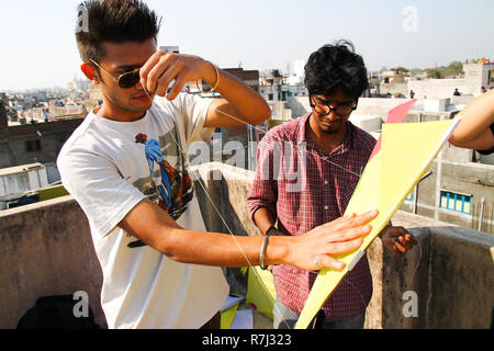 Ahmenabad, India - 8 january 2017: young boys gather above rooftops preparing to celebrate traditional hindu kite festival at sunset flying kites in t - Stock Photo