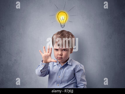 Adorable little kid mull over in front of a grey wall with idea symbol above his head - Stock Photo