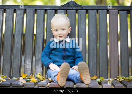 Little boy on a bench in the autumn park. - Stock Photo