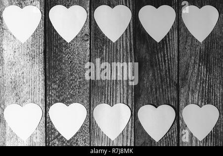 frame of paper hearts on wooden retro grunge background with copy space, top view flat lay, black and white photo - Stock Photo