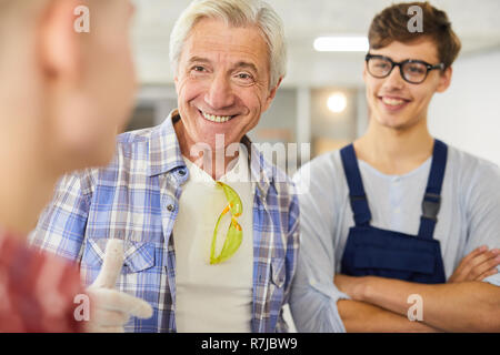 Smiling carpenter teaching young students at woodworking class - Stock Photo