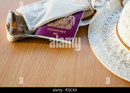 Travel things for travelling abroad British biometric passport in a wallet with women's sunhat on a table top. England, UK, Britain - Stock Photo