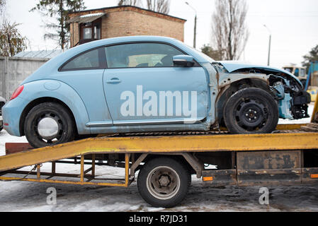 Broken car on tow truck after traffic accident, on the road service. Automobile insurance, safety, repair and transportation. Road dangerous drive. - Stock Photo