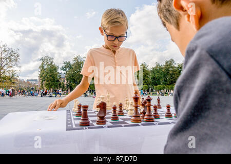.Kids playing chess game in Lukiskes square, Vilnius, Lithuania - Stock Photo